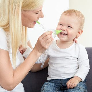 A woman clearing the nose of her smiling son with the help of the Nosiboo Eco Manual Nasal Aspirator