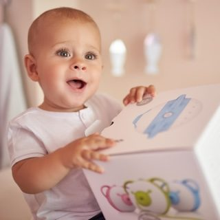 A fascinated baby boy holding a box with the Nosiboo Pro Electric Nasal Aspirator