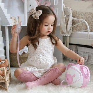 A stylish little girl in her room with the pink Nosiboo Pro Electric Nasal Aspirator