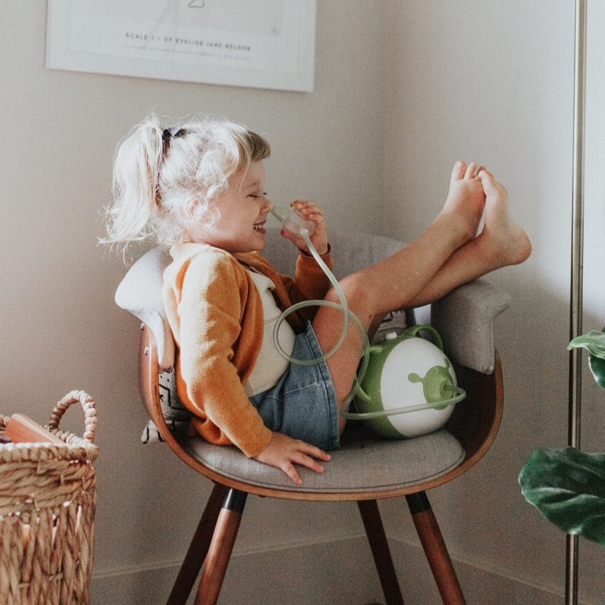 A happy little girl sitting on a chair with the Nosiboo Pro Electric Nasal Aspirator