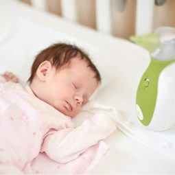 Open the picture of a newborn lying in the baby cot bed, next to the Nosiboo Go Portable Nasal Aspirator