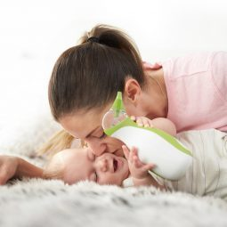 A mom kissing her baby boy who is carrying the Nosiboo Go portable nasal aspirator in his hands while lying on the bed